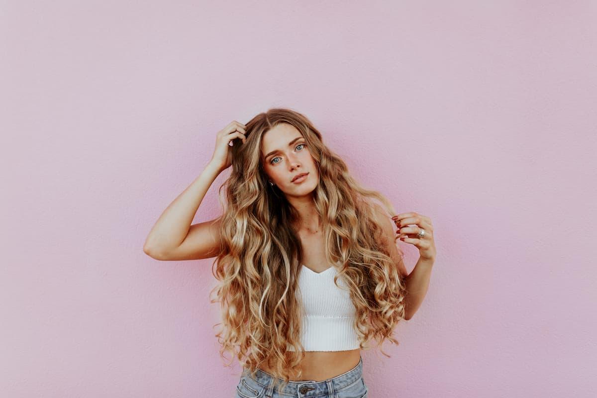 Šioje nuotraukoje mergina ilgais garbanotais plaukais rožiniame fone.
