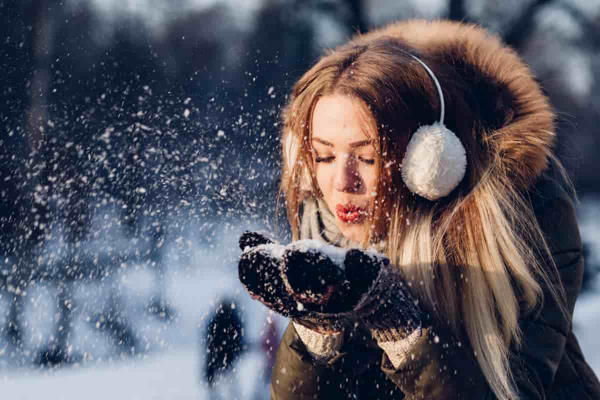 Mergina žiemos metu lauke pučia sniegą nuo delnų.